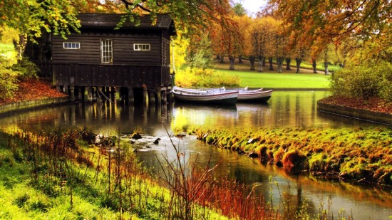 Idyllic country cottage on a river with two boats tied to a dock out front